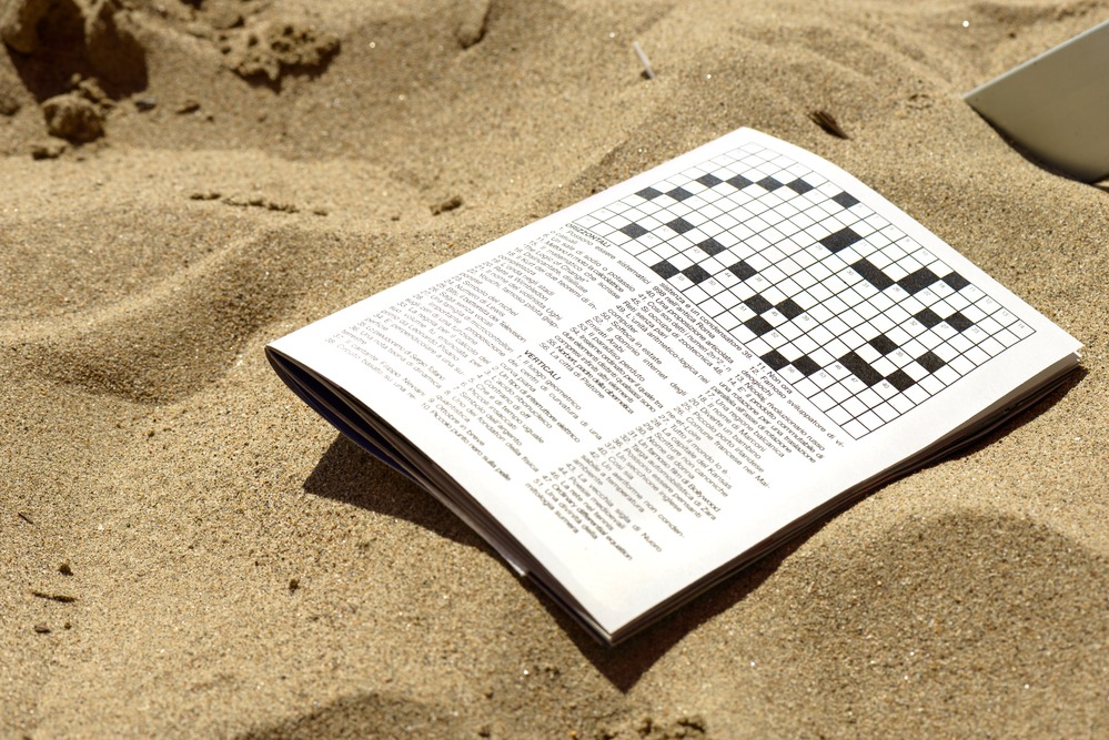 A crosswords game book on the sand