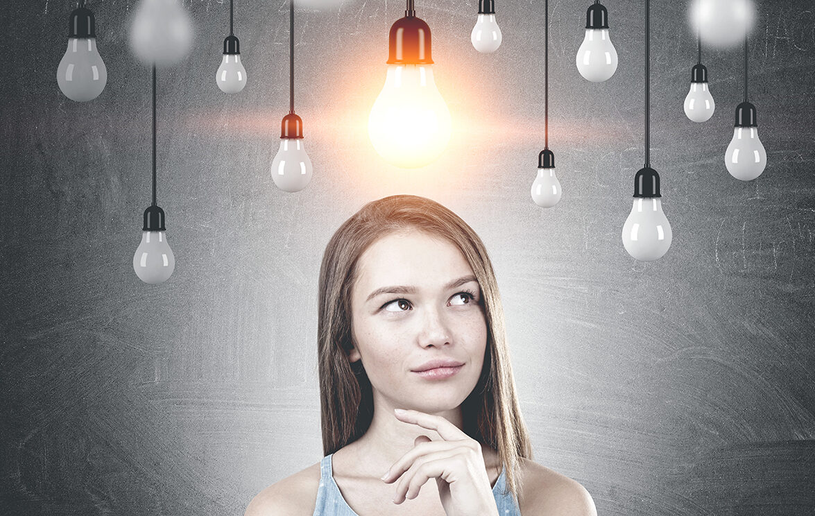 Portrait of a young woman with long fair hair wearing a blue dress and thinking. A blackboard background with many lightbulbs. One is lit.
