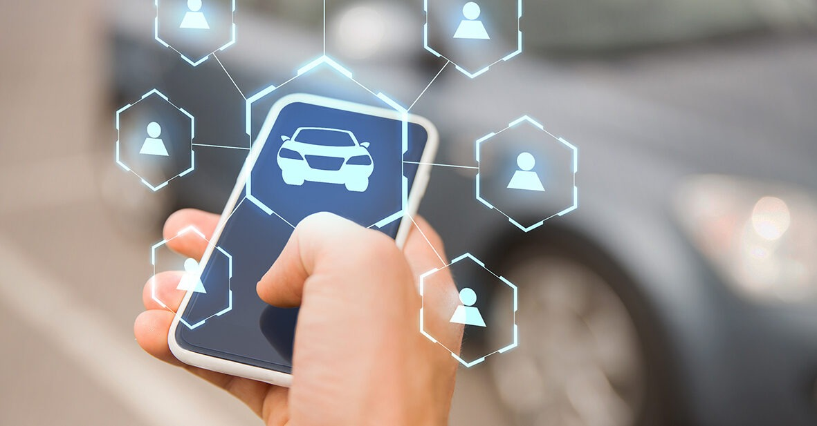 business, transportation and future technology concept - close up of businessman hand with smartphone and virtual car sharing icons