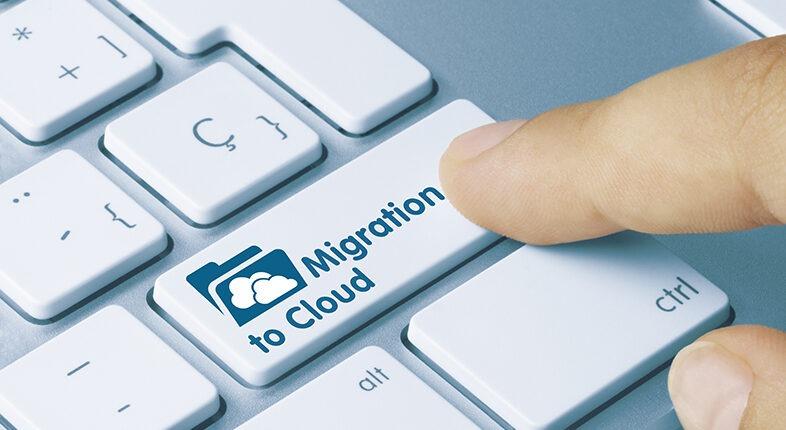 Migration to Cloud Written on Blue Key of Metallic Keyboard. Finger pressing key.