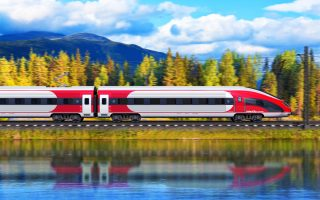 Creative abstract railroad travel and railway tourism transportation industrial concept: scenic summer view of modern high speed passenger train on tracks with lake or sea and mountains in background with motion blur effect